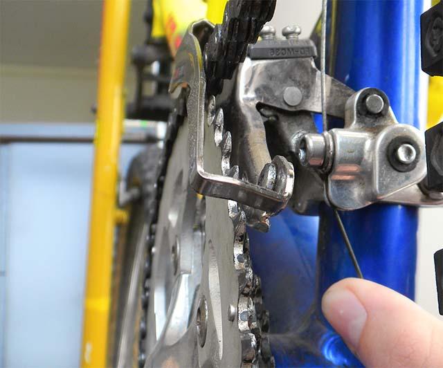 Проверка зазора между цепью и внешней пластиной держателя переднего переключателя